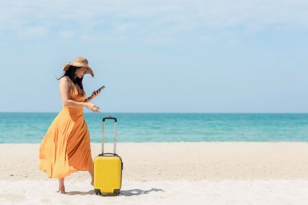 Asian women traveler holding yellow luggage walking and check in smart phone on the beach. Traveler and Tourism planning trips summer vacations with Traveler accessories summertime. Summer Concept  Stock Photo