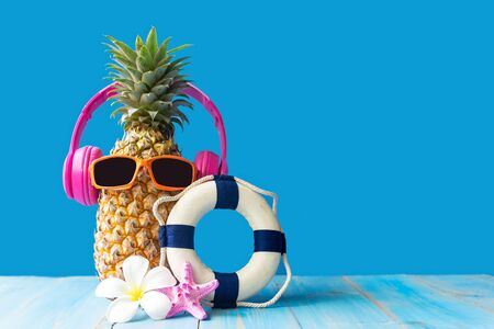 Summer in the party.  Hipster Pineapple Fashion in sunglass and music bright beautiful color in holiday, Creative art fruit for tropical style on the beach vibes, blue background.  Fashion Summer Vacation Concept