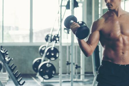 Bodybuilder man exercise  with dumbbell at the gym workout for healthy care and building body.  Fitness instructor exercising the fitness. Diet and Healthy sport Concept 版權商用圖片
