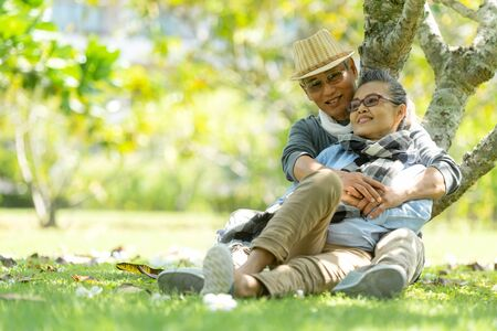 Asian Lifestyle senior couple hug and sitting in the nature park happy in love romantic and relax time. Tourism elderly family travel leisure and activity after retirement in vacations.