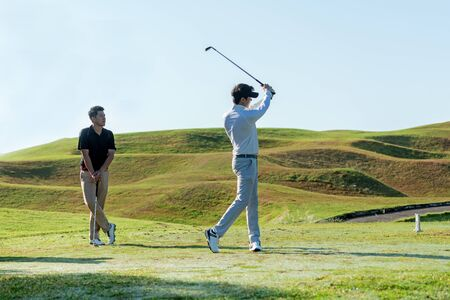 Professional golfer asian two man approach on the tee off for swing and hitting golf ball and looking fairway in course. Hobby in holiday and vacations in sunny morning day on club golf. Lifestyle, and sport Concept.