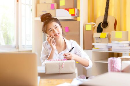 Asian smiling young women owner business calling received order shopping from customer online and packing product. Lifestyle for working at home.