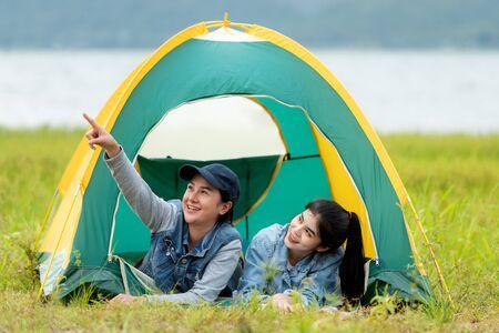 Camping im Freien. Gruppenfreunde Camping Freizeit und Zielreisen. Familie, die am Lagerfeuer sitzt und Gitarre und gebratene Würste spielt, Tourismus entspannen und im Urlaub in der Nähe des Flusses reisen.