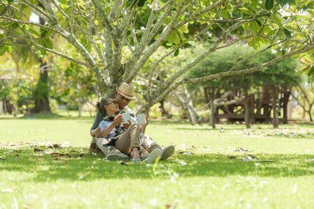 Asiatische Lifestyle Senioren im Ruhestand Ehepaar trinken Kaffee im Naturpark glücklich und entspannen sich. Ältere Familie die Ruhe und Entspannung nach der Pensionierung in den Ferien. Standard-Bild