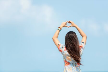 Summer Vacation. Traveler women relaxing and raise hand heart shape joy fun on the beach, so happy and luxury and destination in holiday summer. Tourism chill on sand.