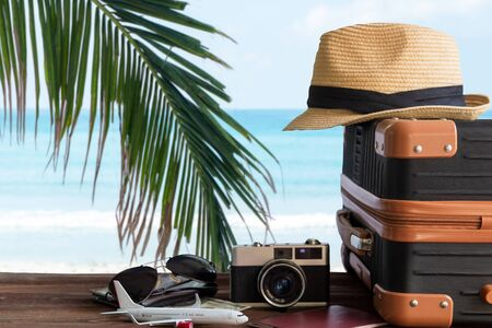 Summer travel and plan with vintage suitcase luggage and old camera in the sand beach. Travel in the holiday trips, airplane.  blue sky background. Summer and Travel Concept Stock Photo