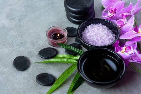 Purple orchid flower nature aromatherapy  oil Spa with candle and stone spa. Thai Spa relax Treatments and massage concrete background. Healthy Concept. Top view and Copy space for text Stock Photo