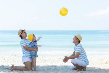Asian happy family have fun and play yellow ball on the beach.  Family people tourism travel in summer and holiday for destination leisure.  Travel and Family Concept Stock Photo - 137181491