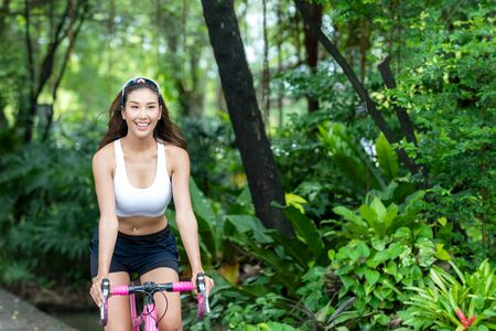 Healthy lifestyle sporty asian woman riding bicycles in city park. People relax and chill in the outdoor. Lifestyle and healthy Concept