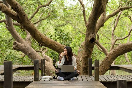 Asian women working and drinking coffee after education nature and forest input the laptop under big tree. The mangrove forest nurture environmental and reduce global warming earth. Ecology Concept Stock fotó