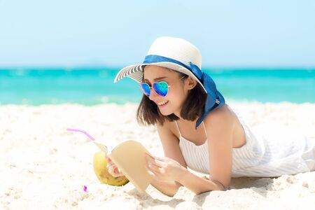 Lifestyle young woman relax on the summer beach. Asia tourism people reading and chill in holiday. blue sky background. Summer Vacations Concept. Foto de archivo