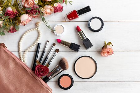 Valentine Gift. Makeup cosmetics tools background and beauty cosmetics, products and facial cosmetics package lipstick, eyeshadow with flower rose, Pearl necklace, vintage tone. Lifestyle and Valentin