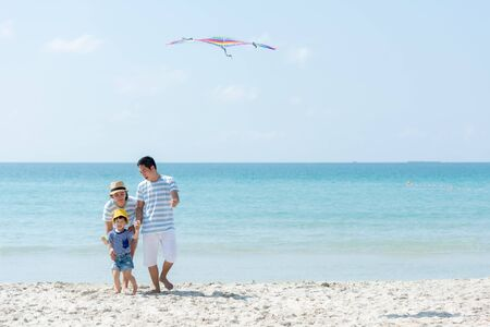 Happy family summer sea beach vacation. Asia youngpeople lifestyle travel play kite enjoy fun and relax in holiday. Travel and Family Concept