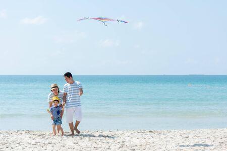 Joyeuses vacances d'été en famille à la plage. Les jeunes d'Asie jouent au cerf-volant de style de vie, s'amusent et se détendent en vacances. Concept de voyage et de famille