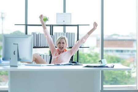 Relax working. Business woman raise hand and relax after job working hard. Young people celebrating growth work for success and together report. Partner happy with your work. Business Concept