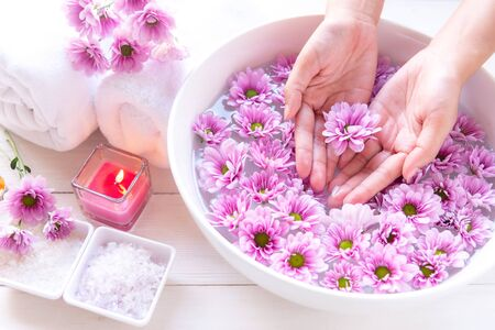 Spa treatment and massage product for female feet and manicure nails spa with pink flower. Woman happy and relax with spa massage Thai. Healthy and Beauty Concept.