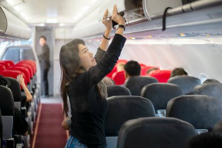 People traveler and tourism woman open overhead locker on airplane and airport for travel trip in summer and holiday time. Travel Concept