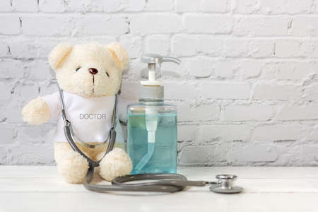 Take care doctor.  Teddy bear doctor with protective medical mask and stethoscope. Hand Sanitizer alcohol gel for hand hygiene protection Coronavirus, white Background.  Covid Virus.  Health Concept