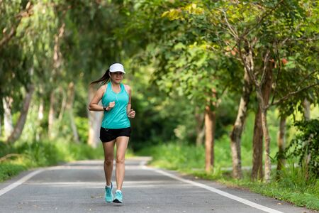Healthy woman jogging run and workout on road outdoor. Asian runner people exercise gym with fitness session, nature park background. Healthy and Lifestyle Concept. Stok Fotoğraf