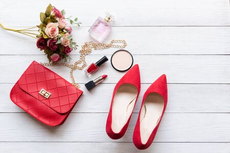 Fashion bag and shoe woman accessories background. Trendy fashion luxury handbag , shoe, perfume and cosmetic design with rose flower. Lifestyle and Beauty Concept