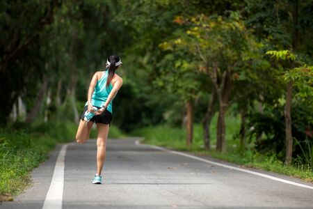Healthy smiling woman warming down stretching her legs and looking away in the road outdoor. Asian runner woman workout before fitness and jogging session at the park. Health care Lifestyle Concept. Stok Fotoğraf
