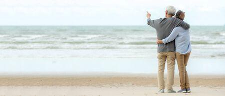 Starsza para azjatyckiego stylu życia przytula się i wskazuje na plaży szczęśliwy w miłości romantyczny i relaksujący czas. Ludzie turystyka starsza rodzina podróżuje wypoczynek i aktywność po przejściu na emeryturę w wakacje i lato, kopia przestrzeń i baner Zdjęcie Seryjne