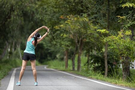 Healthy woman warming up before jogging run and relax stretching her arms and looking away in the road outdoor. Asian runner people workout fitness session, nature park background. Healthy and Lifestyle Concept.