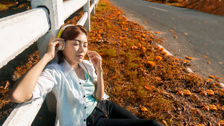 Lifestyle people girl relax and listening music and work from home on the grass in nature park outdoors. Young Woman stay home and resting in summer vacations.