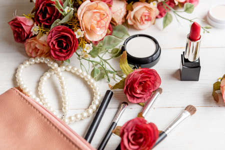 Valentine Gift. Makeup cosmetics tools background and beauty cosmetics, products and facial cosmetics package lipstick, eyeshadow with flower rose, Pearl necklace, vintage tone. Lifestyle and Valentine