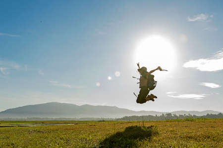 Young woman travel and explore adventure pointing  in nature. Asian people jumping relax for destination leisure landscape forest in summer day. Travel and lifestyle Concept Stock Photo