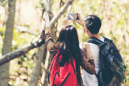 Tourist and traveler asian couple backpack enjoy happy take a photo selfie in the jungle forest nature park . Traveler going camping and explore outdoors destination leisure.