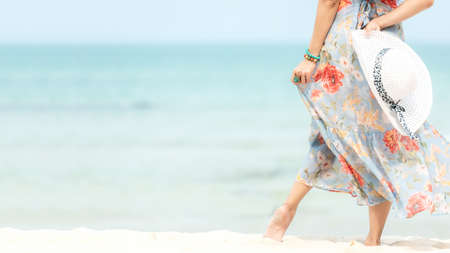 Summer Holiday. Lifestyle woman chill holding big white hat and wearing dress fashion summer trips standing chill on the sandy ocean beach. Happy people enjoy and relax vacation. Lifestyle and Travel Concept Stock Photo