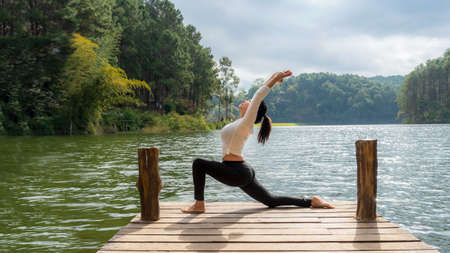 Healthy Yoga woman lifestyle balanced practicing meditate and energy yoga on the bridge in morning and sunset outdoors nature. Healthy life Concept