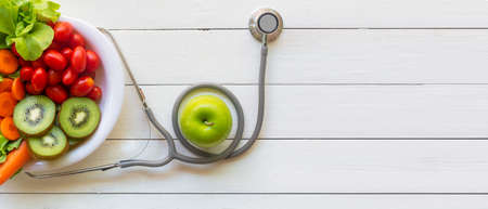 Health Care.  Fresh vegetable salad and green apple with medical stethoscope for diet and weight loss for healthy care and protect virus,  white wooden background.  Copy space and banner for text.  Healthy Life Concept