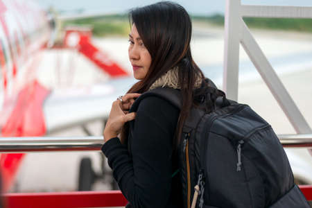 Traveler woman plan and backpack see airplane flight at the airport glass window, girl tourist happy hold bag and waiting luggage in hall airplane departure. Business people trip and Travel Concept Stock Photo
