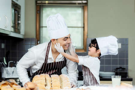 Cooking Family. Chef kid boy enjoy and funning cooking toast and make  bread with father.  Asian son help father making sweet food, so happy and education.  Family Lifestyle Concept
