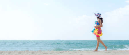 Summer Vacation. Lifestyle woman walking relax and happy on beach tropical outdoor in summer day. Young people luxury and travel destination in holiday. Tourism chill leisure of trips. copy space for banner