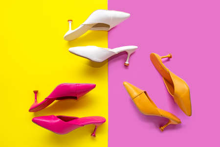 Top View. Fashion shoe woman accessories set. Trendy color full fashion shoes heels. Pink and Yellow pastel color background. Fashion Concept.