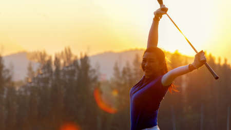 Golfer woman cheerful happy and relax with a golf in the golf club in the sunny and evening sunset time.  Golfer sport course golf ball fairway in the sunny and evening sunset time. People lifestyle woman playing game golf tee of on the green grass. Healthy and Sport outdoor