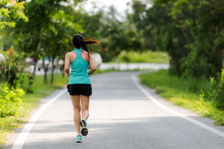 Healthy woman jogging run and workout on road outdoor. Asian runner people exercise gym with fitness session, nature park background. Healthy and Lifestyle Concept. Stock Photo