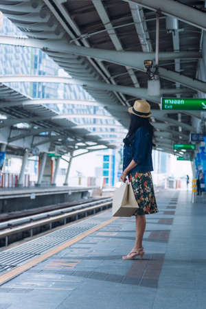 People waiting for the train at subway station. Asian tourist women staying on a line and waiting to board the train Stock Photo