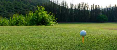Close up Golf club hitting golf ball along fairway towards green with copy space, green nature background. Lifestyle and Healthy Concept, copy space and banner