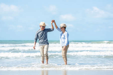 Retirement Travel. Asian Lifestyle senior couple dancing on the beach happy and relax time. Tourism elderly family travel leisure and activity after retirement in vacations and summer. Stock Photo