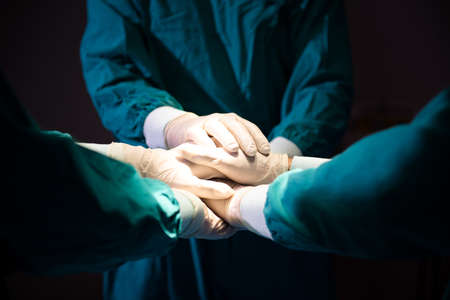 Group Surgeon doctor joining hands before Patient surgery in hospital operating theater .   Teamwork medical doctor working  performing surgery Stok Fotoğraf