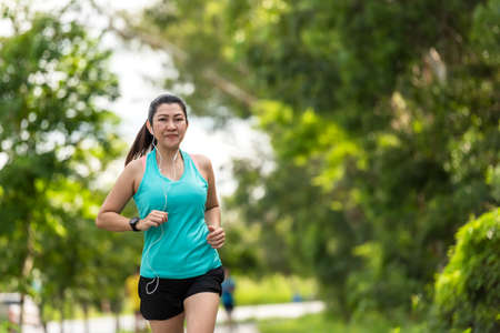 Healthy woman jogging run and workout on road outdoor. Asian runner people exercise gym with fitness session, nature park background. Health and Lifestyle Concept. 版權商用圖片