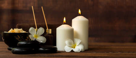 Thai spa composition treatments aroma therapy with candles and Plumeria flowers on wooden table. Healthy and Relax Concept