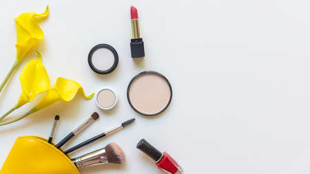 Makeup beauty cosmetic fashion set background. Cosmetics woman bag product facial, lipstick and items decorative composition with yellow lily on white background, copy space and banner for text. Lifestyle Concept