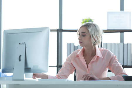 Businesswoman caucasian using  computer to work with financial data in the modern office, relax and rest time after work.  Business Concept.