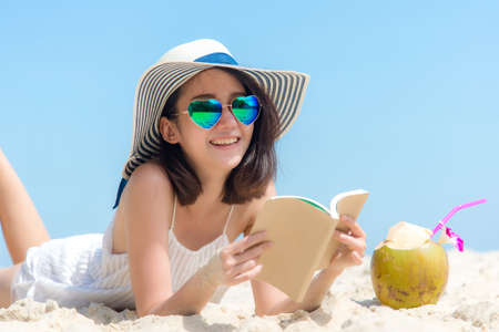 Lifestyle young  woman relax on the summer beach.  Asia tourism people reading and chill in holiday. blue sky background.  Summer Vacations Concept.