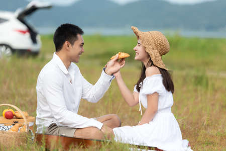Lifestyle couple happy honeymoon in sunny time. Asian young couple sitting picnic and relax in the meadow and field near river and mountain in holiday.  Romantic and In love.  Lifestyle concept